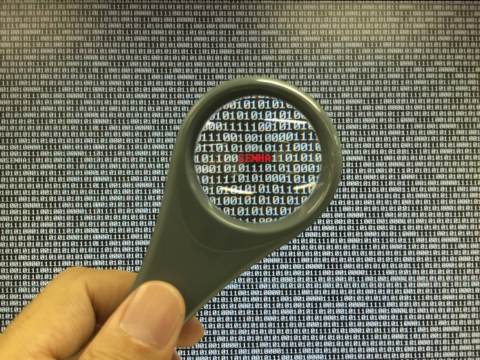 hand holding a magnifying glass over binary data